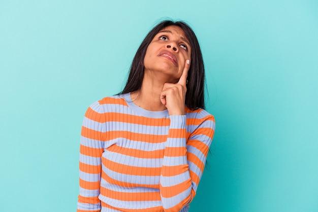 Jonge latijnse vrouw geïsoleerd op blauwe achtergrond huilen, ongelukkig met iets, pijn en verwarring concept.