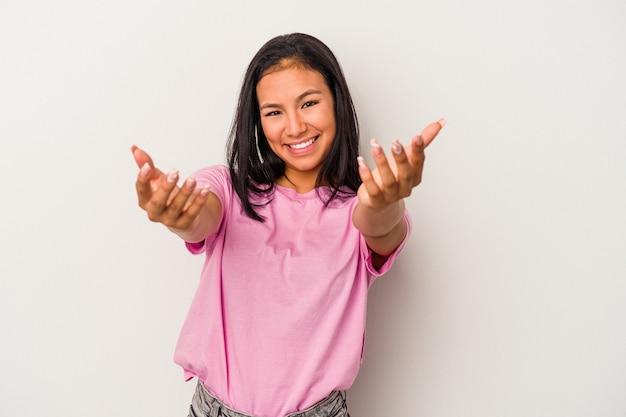Jonge latijnse vrouw geïsoleerd op een witte achtergrond voelt zich zelfverzekerd en geeft een knuffel aan de camera.