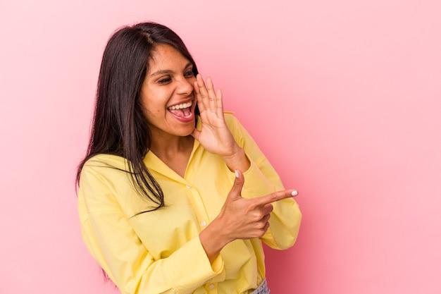 Jonge latijnse vrouw geïsoleerd op roze achtergrond die een roddel zegt, wijzend naar de zijkant die iets meldt.