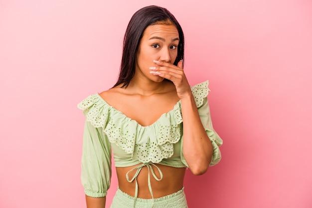 Jonge latijnse vrouw geïsoleerd op roze achtergrond die mond bedekt met handen die bezorgd kijken.