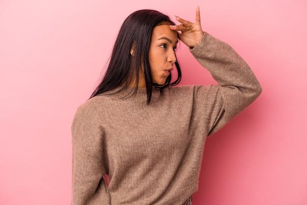 Jonge latijnse vrouw geïsoleerd op roze achtergrond die ver weg kijkt en hand op het voorhoofd houdt.