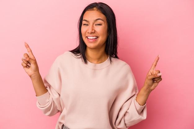 Jonge latijnse vrouw geïsoleerd op roze achtergrond geeft aan dat met beide voorvingers een lege ruimte wordt weergegeven.