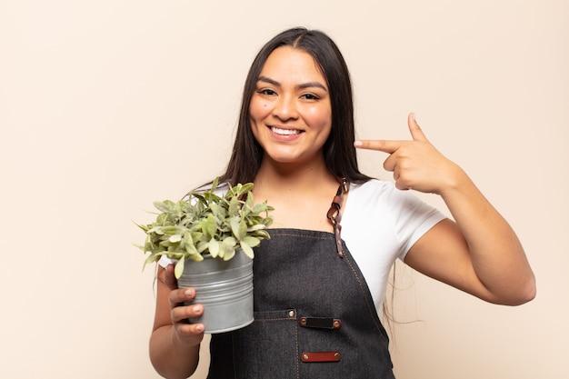 Jonge latijnse vrouw glimlachend vol vertrouwen wijzend naar eigen brede glimlach, positieve, ontspannen, tevreden houding