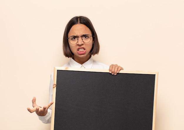 Jonge latijnse vrouw kijkt boos, geïrriteerd en gefrustreerd schreeuwend wtf of wat is er mis met je?