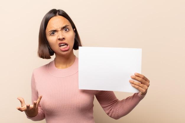Jonge latijnse vrouw kijkt boos, geïrriteerd en gefrustreerd schreeuwend wtf of wat is er mis met je