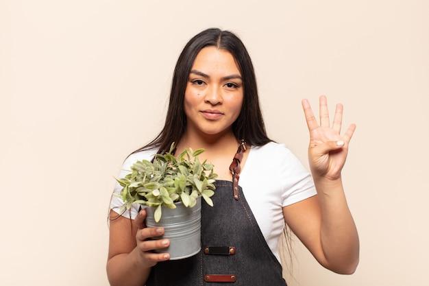 Jonge latijnse vrouw lacht en ziet er vriendelijk uit, met nummer vier of vierde met de hand naar voren