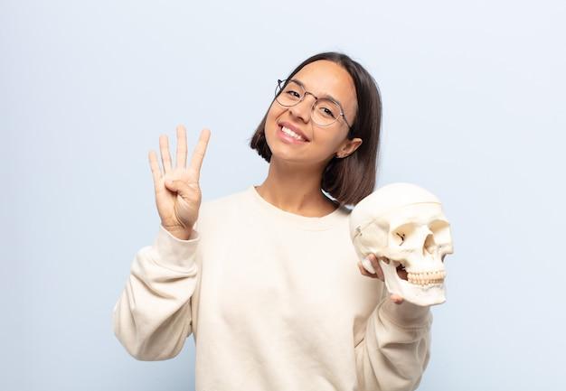 Jonge latijnse vrouw lacht en ziet er vriendelijk uit, nummer vier of vierde met hand naar voren tonend