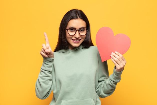 Jonge latijnse vrouw lacht en ziet er vriendelijk uit, toont nummer één of eerst met de hand naar voren, aftellend