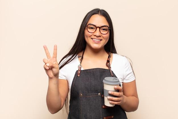 Jonge latijnse vrouw lacht en ziet er vriendelijk uit, toont nummer twee of seconde met de hand naar voren, aftellend