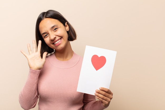 Jonge latijnse vrouw lacht en ziet er vriendelijk uit, toont nummer vijf of vijfde met hand naar voren, aftellend