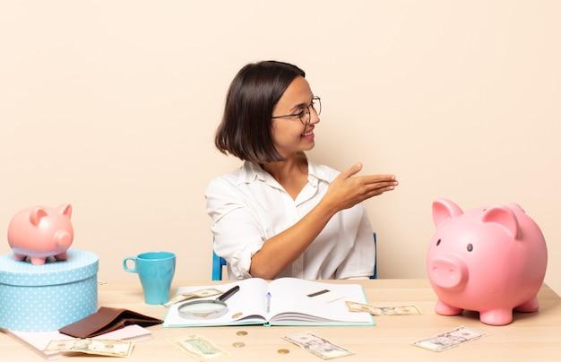 Jonge latijnse vrouw lacht, groet je en biedt een handdruk om een succesvolle deal te sluiten