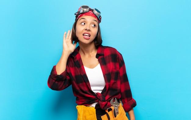 Jonge latijnse vrouw lacht, kijkt nieuwsgierig opzij, probeert te luisteren naar roddels of een geheim af te luisteren