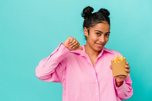 Jonge latijnse vrouw met chips geïsoleerd op blauwe achtergrond voelt zich trots en zelfverzekerd, voorbeeld om te volgen.