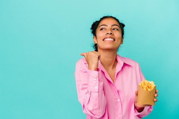 Jonge latijnse vrouw met chips geïsoleerd op blauwe achtergrond wijst met duimvinger weg, lachend en zorgeloos.