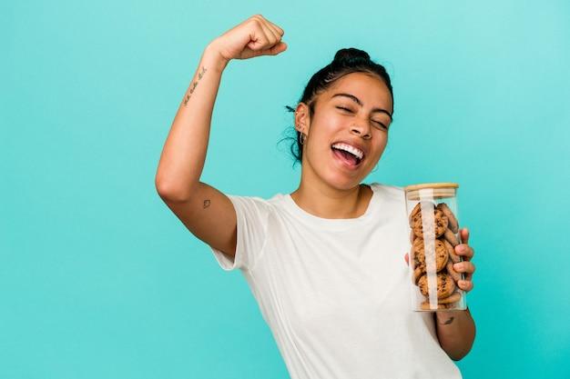 Jonge latijnse vrouw met een koekjespot geïsoleerd op een blauwe achtergrond die vuist opheft na een overwinning, winnaarconcept.