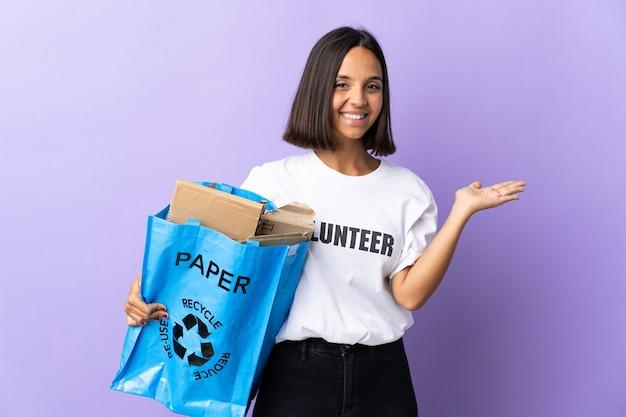Jonge latijnse vrouw met een recyclingzak vol papier om te recyclen geïsoleerd op paars met copyspace denkbeeldig op de handpalm om een advertentie in te voegen