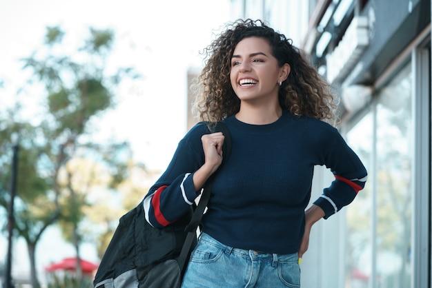 Jonge latijnse vrouw met krullend haar die lacht terwijl ze buiten op straat loopt. stedelijk begrip.