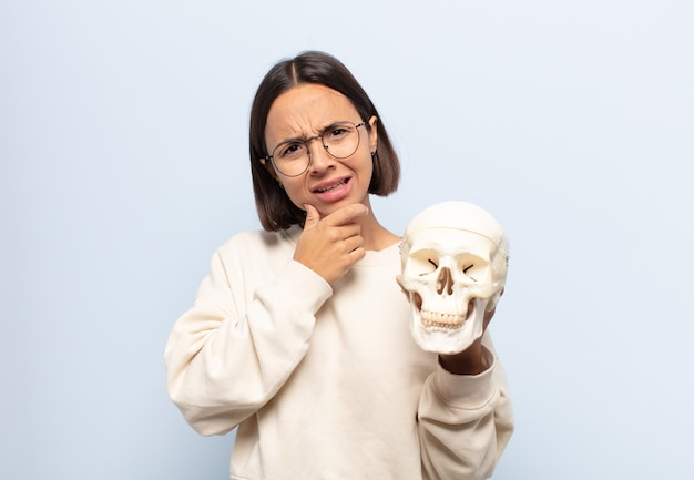 Jonge latijnse vrouw met mond en ogen wijd open en hand op kin, zich onaangenaam geschokt, zegt wat of wauw