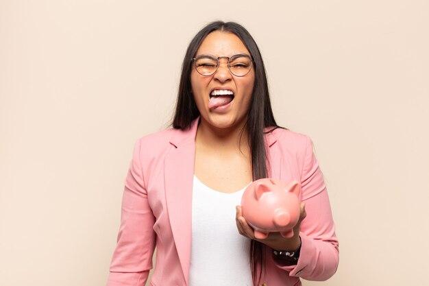 Jonge latijnse vrouw met vrolijke, zorgeloze, rebelse houding, grappen maken en tong uitsteken, plezier maken