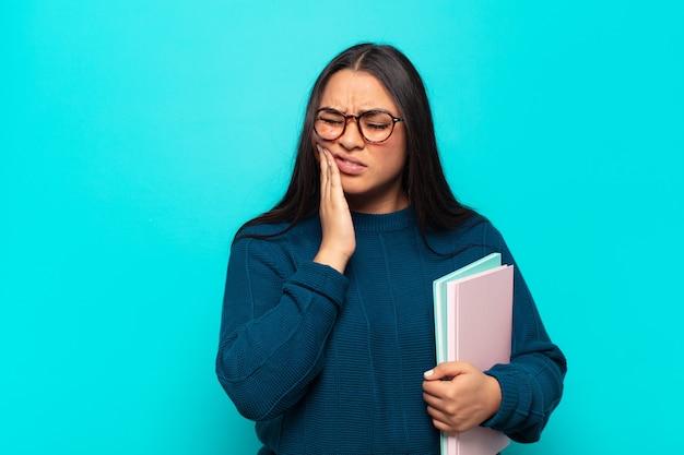 Jonge latijnse vrouw met wang en pijnlijke kiespijn, zich ziek, ellendig en ongelukkig voelen, op zoek naar een tandarts