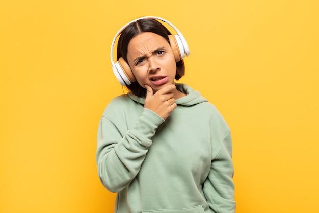 Jonge latijnse vrouw met wijd open mond en ogen en hand op kin, onaangenaam geschokt, wat zeggend of wauw