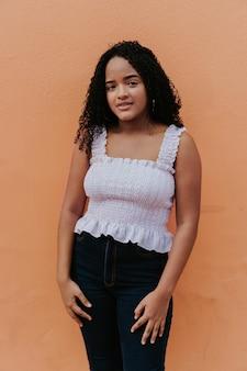 Jonge latijnse vrouw op een oranje achtergrond