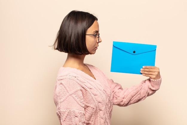 Jonge latijnse vrouw op profielweergave die ruimte vooruit wil kopiëren, denken, fantaseren of dagdromen