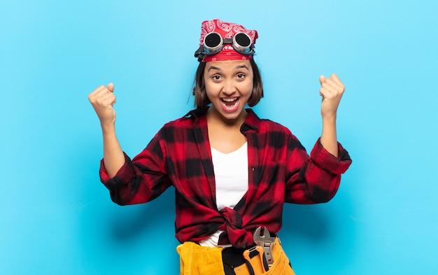 Jonge latijnse vrouw triomfantelijk schreeuwend, eruitziend als een opgewonden, blije en verraste winnaar, vierend
