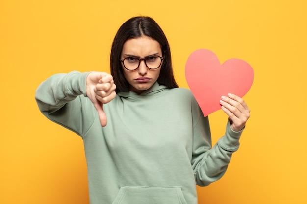 Jonge latijnse vrouw voelt zich boos, boos, geïrriteerd, teleurgesteld of ontevreden, duimen naar beneden met een serieuze blik