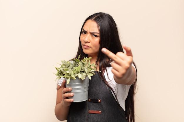 Jonge latijnse vrouw voelt zich boos, geïrriteerd, opstandig en agressief, draait de middelvinger om en vecht terug