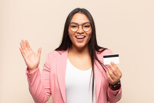 Jonge latijnse vrouw voelt zich gelukkig, verrast en opgewekt, glimlacht met een positieve houding, realiseert een oplossing of idee
