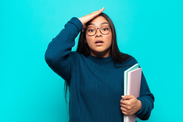 Jonge latijnse vrouw voelt zich geschokt en geschokt, steekt handen tegen het hoofd en raakt in paniek bij een fout