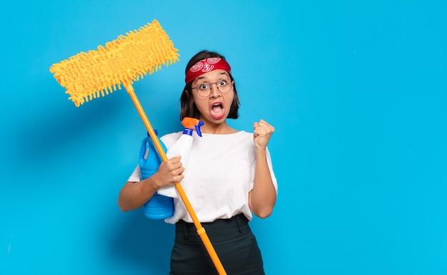 Jonge latijnse vrouw voelt zich geschokt, opgewonden en gelukkig, lacht en viert succes en zegt wow!