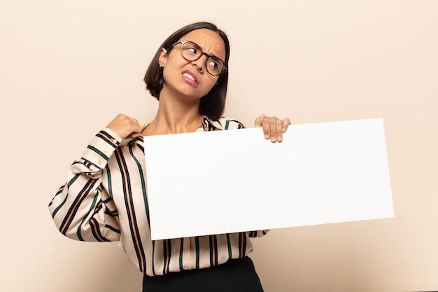 Jonge latijnse vrouw voelt zich gestrest, angstig, moe en gefrustreerd, trekt aan de nek van het shirt, ziet er gefrustreerd uit met een probleem