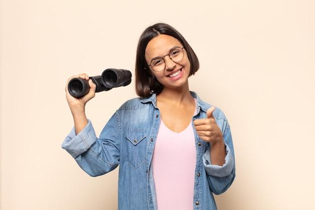 Jonge latijnse vrouw voelt zich trots, zorgeloos, zelfverzekerd en gelukkig, positief glimlachend met duimen omhoog