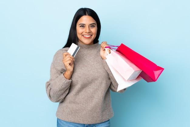 Jonge latijnse vrouwenvrouw die op blauwe holdings het winkelen zakken en een creditcard wordt geïsoleerd