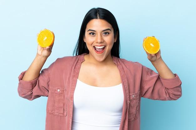 Jonge latijnse vrouwenvrouw die op blauwe muur een sinaasappel houdt