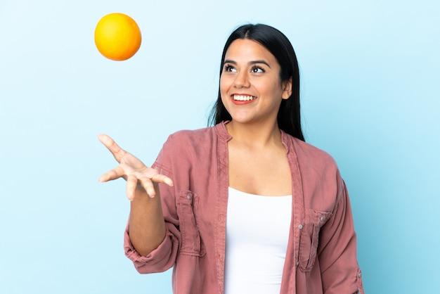 Jonge latijnse vrouwenvrouw die op blauwe muur wordt geïsoleerd die een sinaasappel houdt