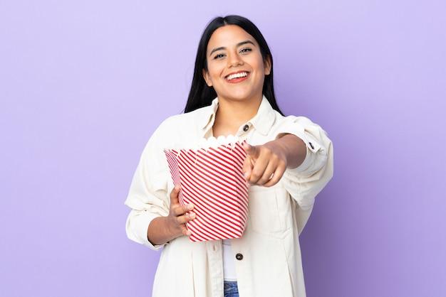 Jonge latijnse vrouwenvrouw die op witte muur een grote emmer popcorns houdt terwijl het richten van voorzijde