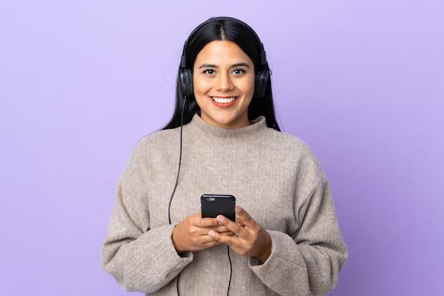 Jonge latijnse vrouwenvrouw op purpere muur het luisteren muziek met mobiel en kijkend voorzijde
