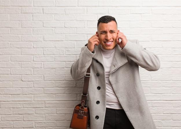 Jonge latijnse zakenman die oren behandelt met handen