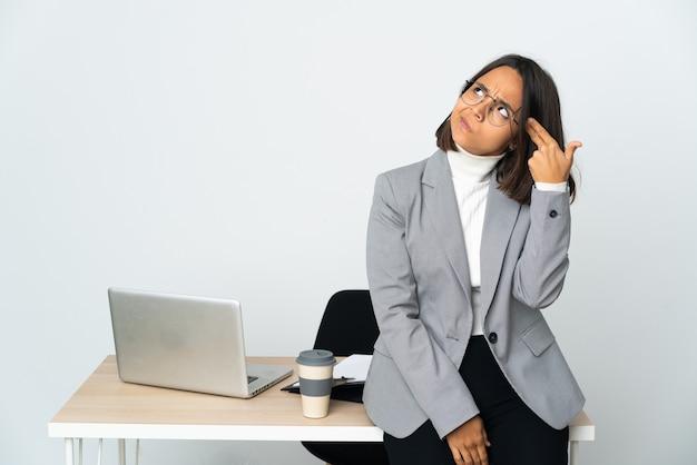 Jonge latijnse zakenvrouw die werkt in een kantoor geïsoleerd op een witte achtergrond met problemen bij het maken van zelfmoordgebaar