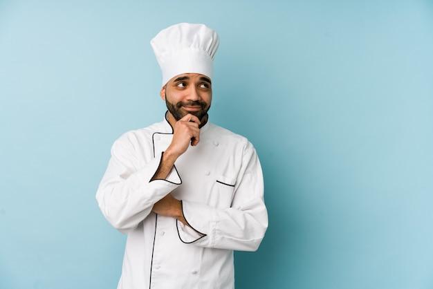 Jonge latin chef-kok man geïsoleerd zijwaarts kijken met twijfelachtige en sceptische uitdrukking.
