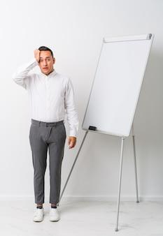 Jonge latin coaching man met een whiteboard geïsoleerd geschokt, ze heeft belangrijke bijeenkomst herinnerd.