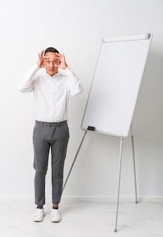 Jonge latin coaching man met een whiteboard geïsoleerd met ogen geopend om een succeskans te vinden.