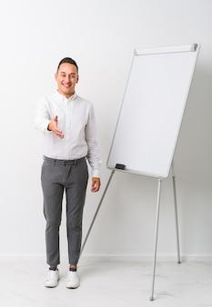 Jonge latin coaching man met een whiteboard geïsoleerd strekken hand in groet gebaar.