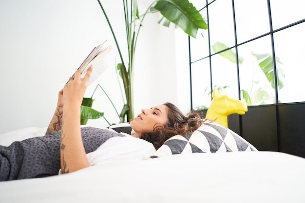 Jonge latina-vrouw die een boek leest dat op het bed ligt, mensen die thuis studeren en leren