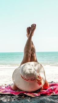 Jonge latina-vrouw die haar benen laat zien terwijl ze op het strand ligt