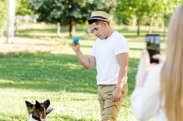 Jonge latino man speelt en traint met zijn border collie-hond terwijl zijn vriendin een foto van hem maakt met haar mobiele telefoon