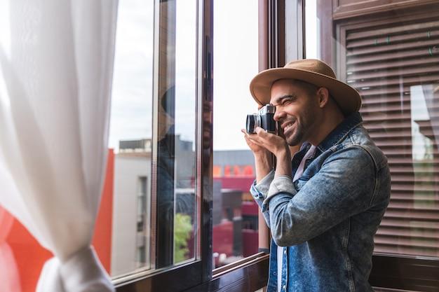 Jonge latino mens die beelden van venster thuis nemen